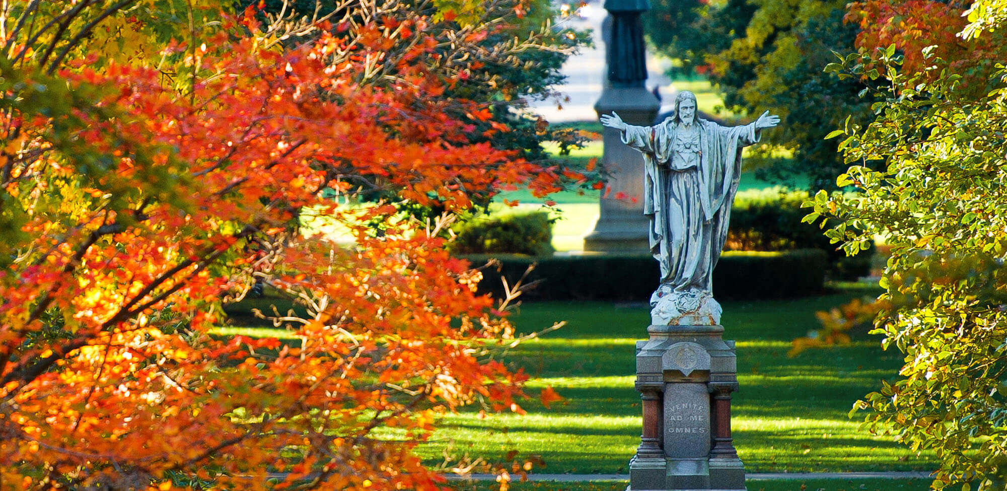 Statue of Jesus with open arms on a fall day.