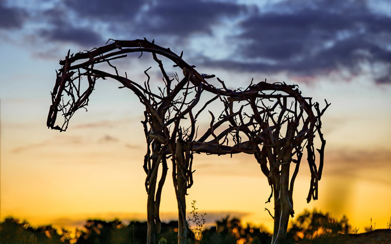 A horse sculpted out of branches stands before a bold yellow and blue sunset.