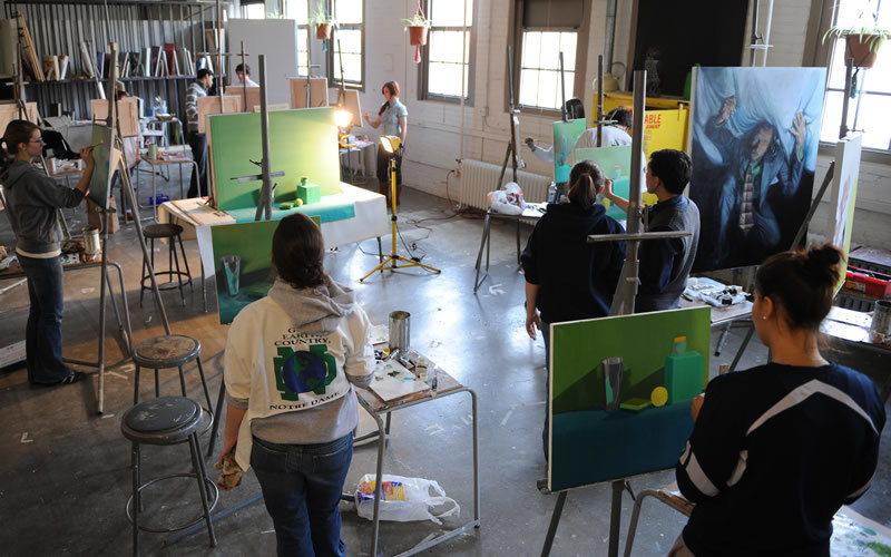 A studio classroom, with students working on paintings.