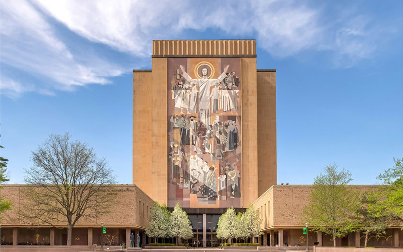 An exterior shot of Hesburgh Library, with the Word of Life mosaic, on a blue sky day.