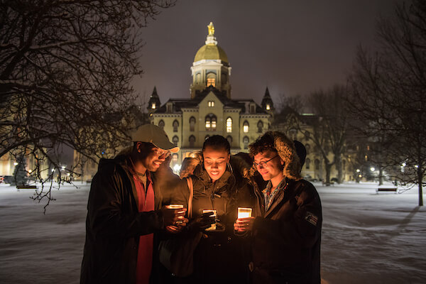 Students hold candles in front of Main Building at night.
