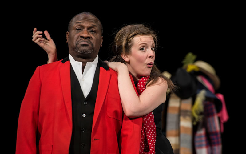 An actress drapes her arms around an actor dressed in a red suit.