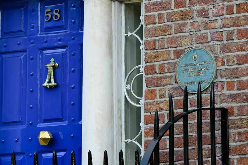 Students by the cobalt blue door to the O'Connell House in Dublin, Ireland.