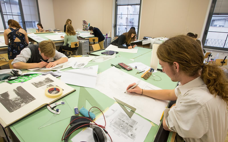 Students work at big studio tables, sketching with rulers and protractors.