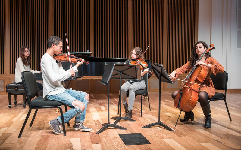Four students, each playing an instrument, perform together on stage.