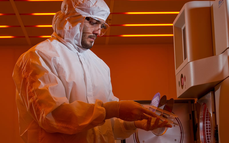 A researcher in a full-body protection suit holds a petri dish by a machine.