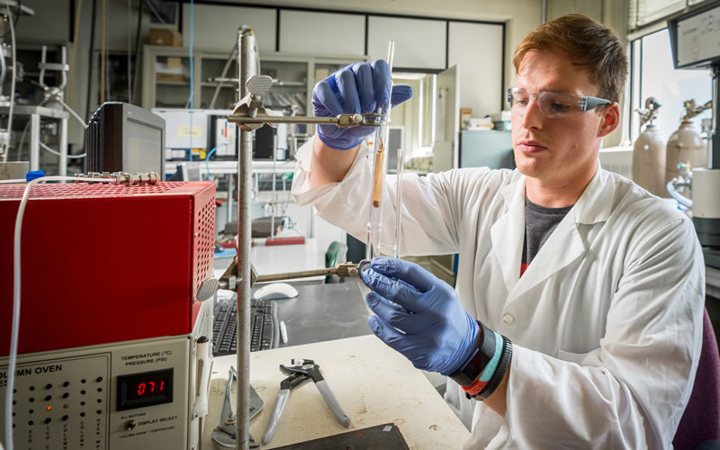 A researcher in a white lab coat and goggles holds a vial near a machine.