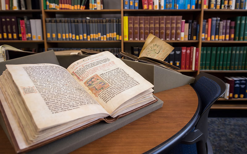 A Medieval book lays open on a table in a library.