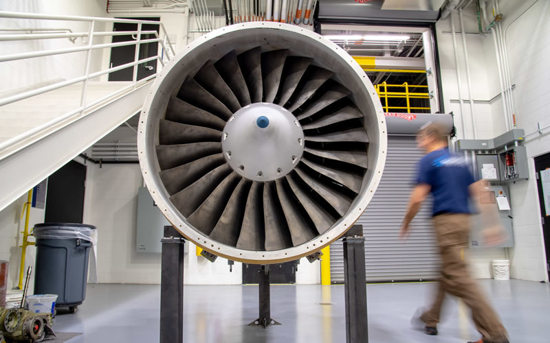 A man walks by a turbomachine in a laboratory.