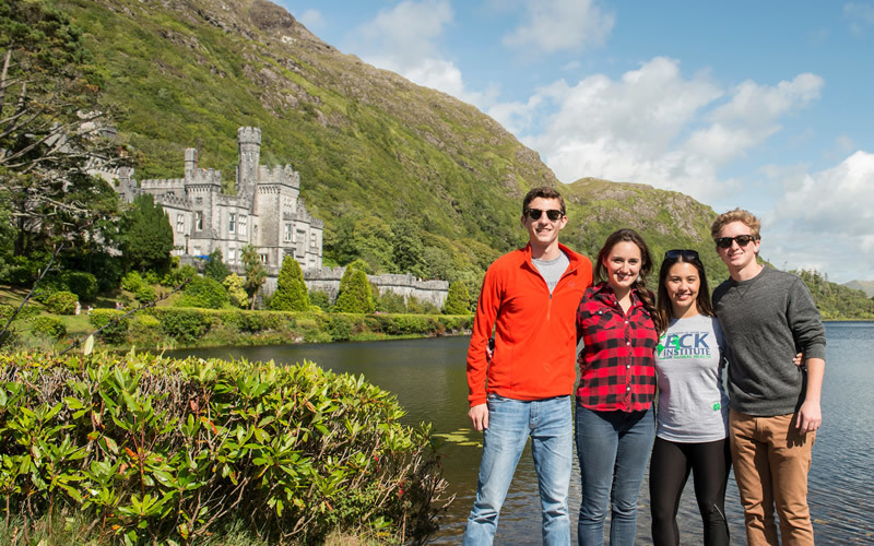 Four students pose in front of Kylemoore Abbey, with lush green bushes and a lake.