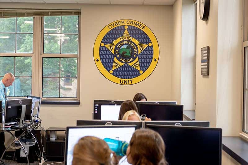 People work at desks under a Cyber Crime Unit badge on the wall.