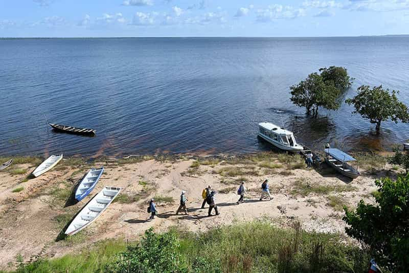People walk on the banks of the Amazon River. Boats are on the shore.